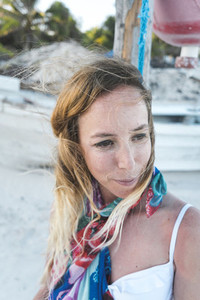 Woman posing near pole on beach