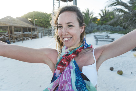 Smiling woman near beam on beach