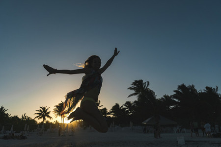 Woman jumping on beach in evening