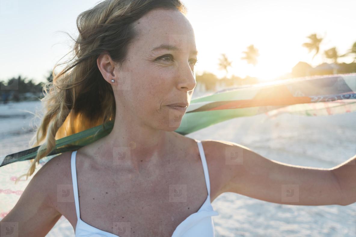 Cheerful woman looking at camera on beach