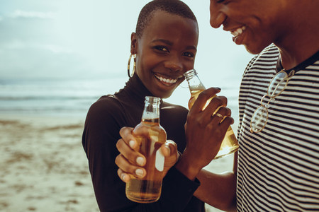 Couple in love drinking beer at beach