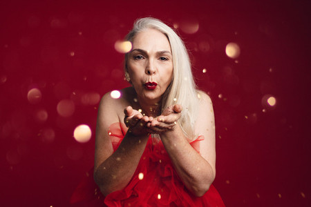 Attractive senior woman blowing glitters