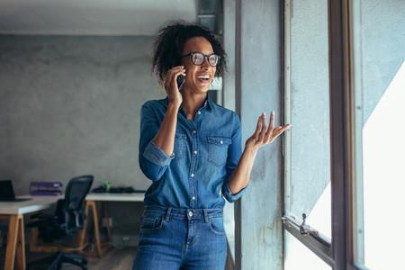 Smiling woman entrepreneur talking over phone