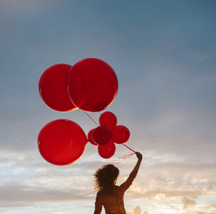Woman with balloons at sunset