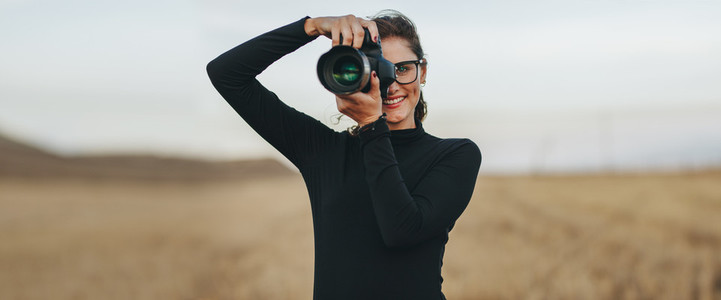 Professional female photographer shooting outdoors