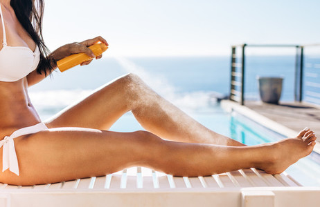 Woman applying suntan spray