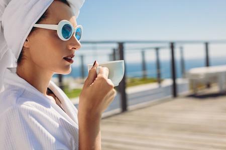 Woman sitting by pool having coffee