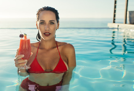 Woman inside a pool with a drink