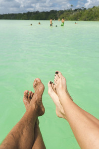 Crop legs over calm sea on resort