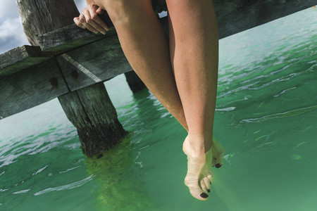 Crop legs over calm sea on resort