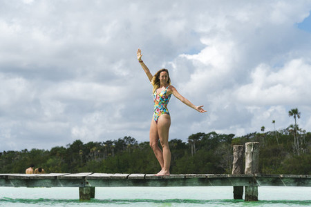 Woman in swimwear standing on pier with open arms