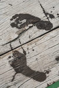 Barefoot wet footprints on old wooden floor