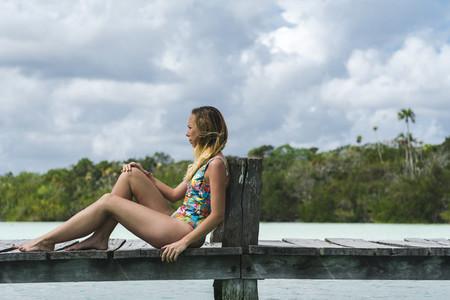 Smiling female sitting on wooden pier on resort
