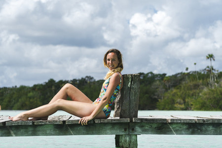 Smiling female sitting on wooden pier on resort