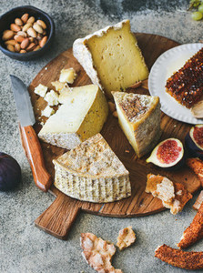 Cheese assortment figs honey fresh bread and nuts