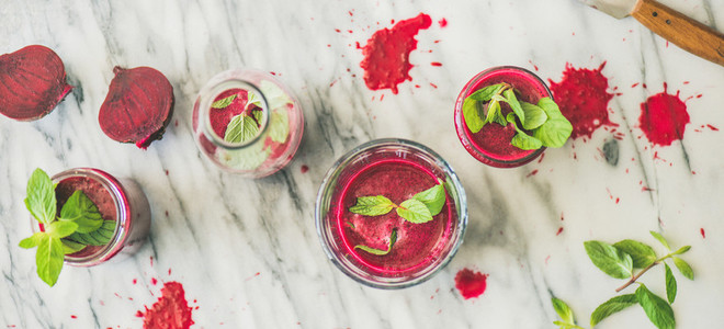 Fresh morning beetroot smoothie or juice in glasses marble background