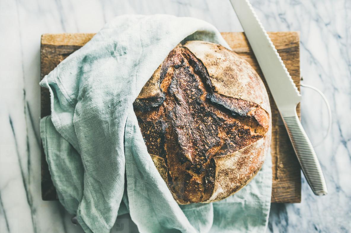 Freshly baked sourdough bread on chopping board