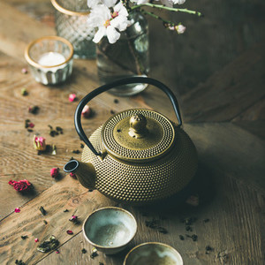 Golden iron teapot  cups  dried rose  candles  almond flowers