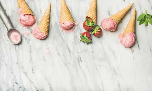 Flat lay of homemade yogurt strawberry ice cream in waffle cones