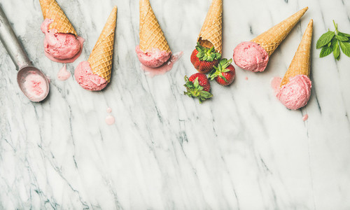 Flat lay of homemade yogurt strawberry ice cream in waffle cones