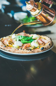 Freshly baked Italian pizza with ham  artichokes served in restaurant