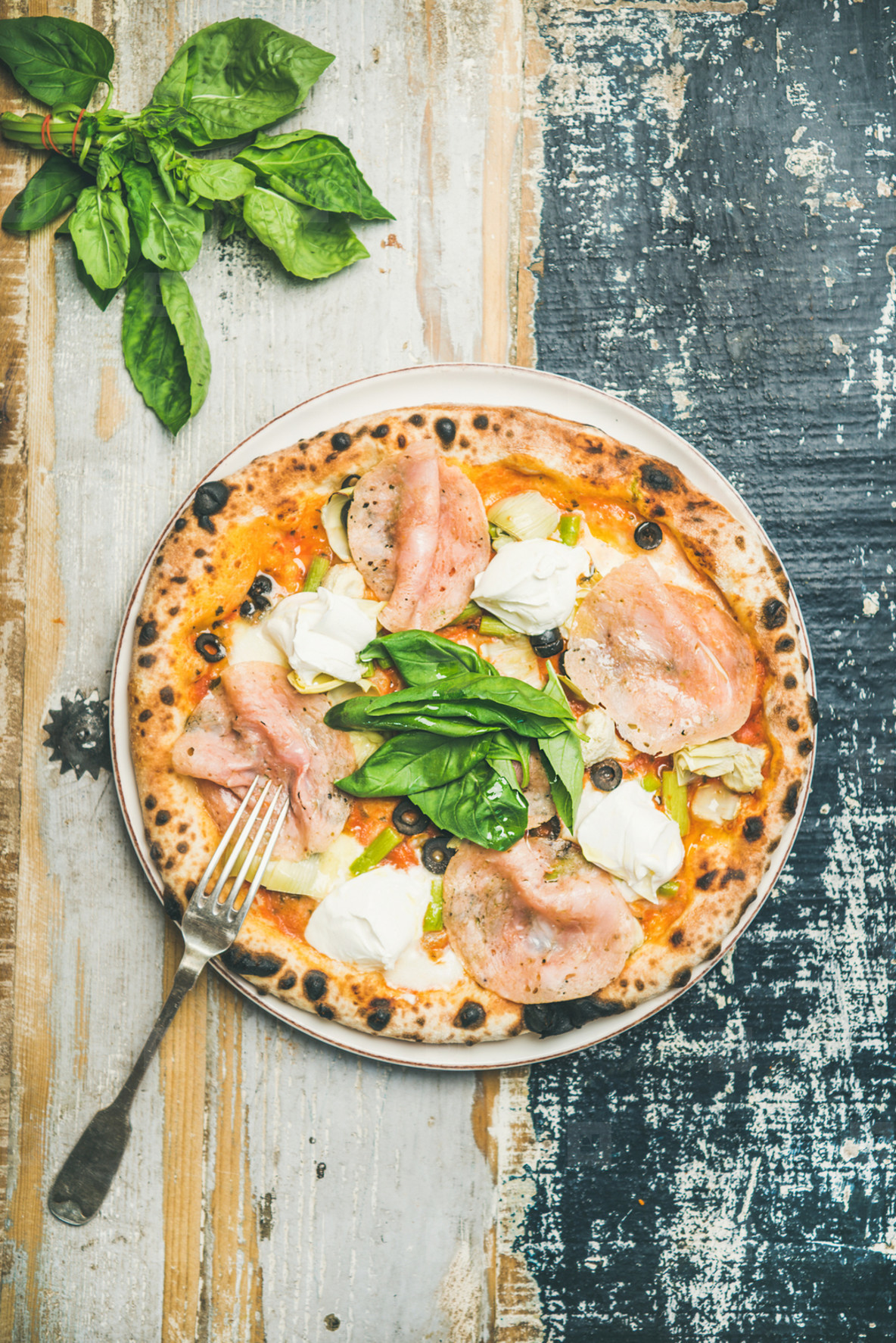Freshly baked pizza with ham  artichokes  cheese  basil on plate