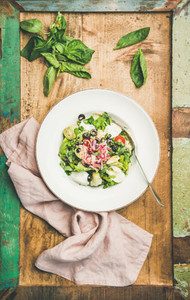 Fresh green summer salad with artichokes over rustic background