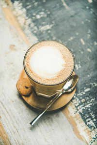 Latte coffee over rustic wooden painted background