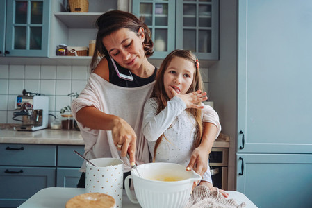 mom teaches her little daughter to cook food