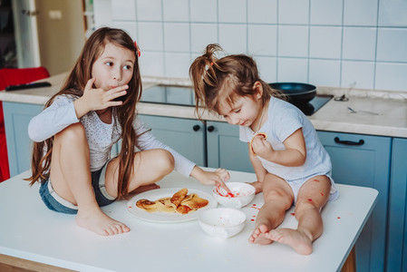 Two little girls in the kitchen sitting on the table