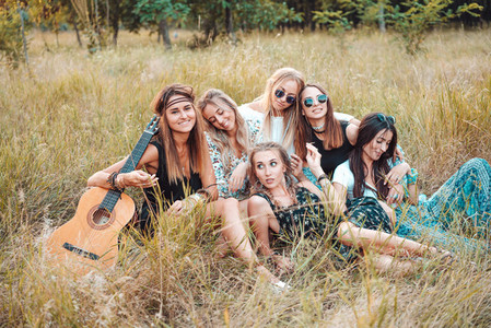 Six girls in nature are sitting on the grass