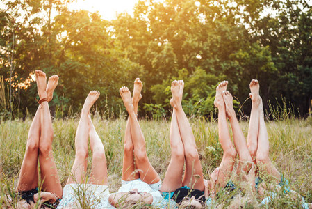 Six girls lie on the grass and raise their legs up