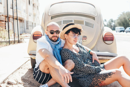 Couple sitting on the asphalt behind the car