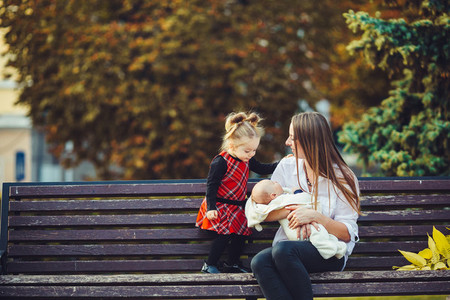 mother and two daughters rest on a bench