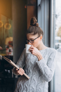 Young girl looking at tablet and smiling in cafe with big window