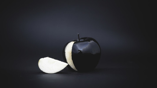 sliced black apple on a background