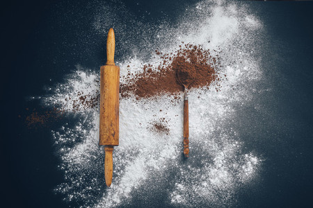 wooden rolling pin with flour and a spoon of cocoa on a black and blue background  Concept creative chaos