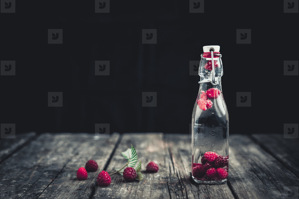 Bottle delicious refreshing drink of raspberry  Wood background