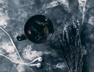 black mug with floating rose inside on marble with white headpho