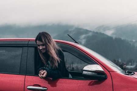 cute girl leaning out of an open car window enjoy background mountains
