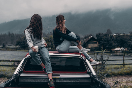 two girls are sitting by the car on a mountains background