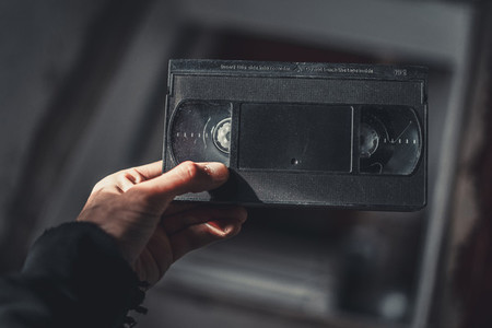 hand holds an old vhs cassette  In the attic