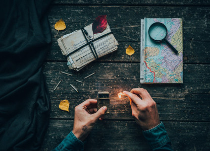 old letters with vintage map and burning match in hands on a wooden table
