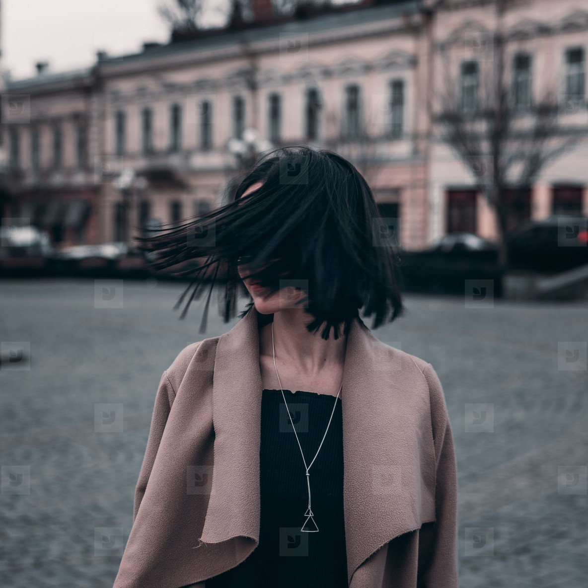 cute brunette in a coat walks around the city