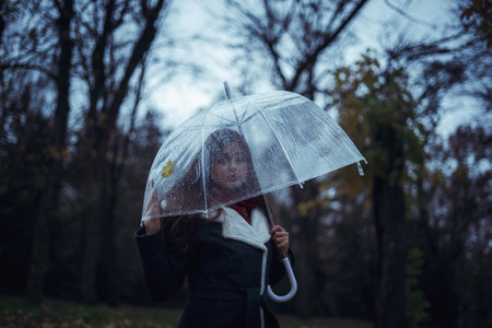 girl holding a transparent umbrella in an autumn park and looking at a fallen leaf  Concept Autumn after Rain