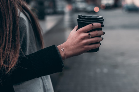 Woman hand with aircraft accessory hold black coffee on city bac
