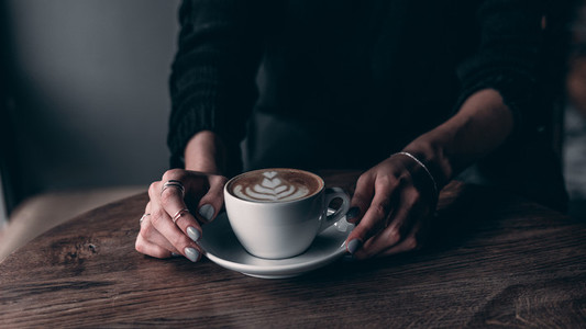girl holding coffee with a pattern