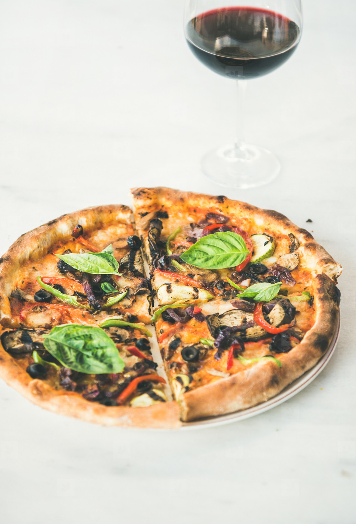 Freshly baked pizza with vegetables  basil and glass of wine