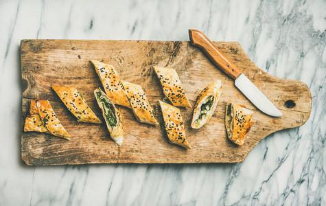 Freshly baked Turkish borek roll slices on wooden board