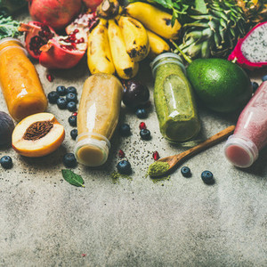 Colorful smoothies in bottles with fresh tropical fruit square crop